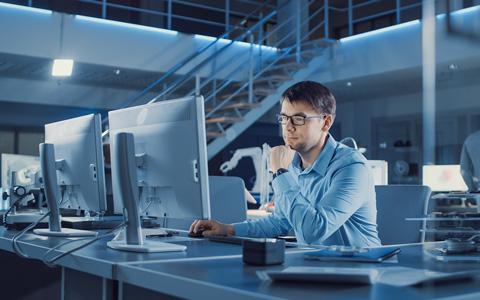berufserfahrener Mitarbeiter arbeitend an seinem Arbeitsplatz